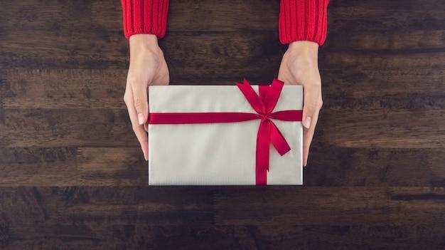 灰色の紙で包まれたクリスマスギフトボックスを与える女性の手