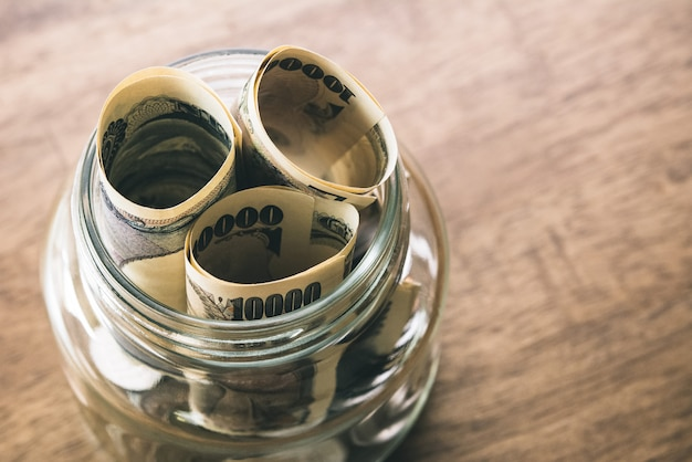 ガラス瓶の中の日本円のお金紙幣のロール