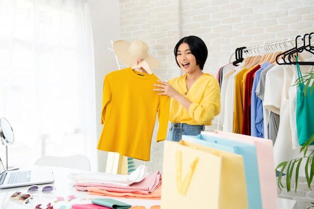服やアクセサリーを示す若いアジア女性ファッションブロガー