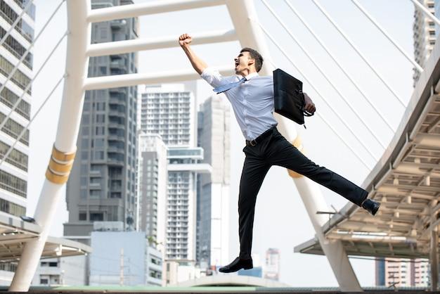 アジア系のビジネスマンが成功したジェスチャーで育った片方の腕でジャンプ