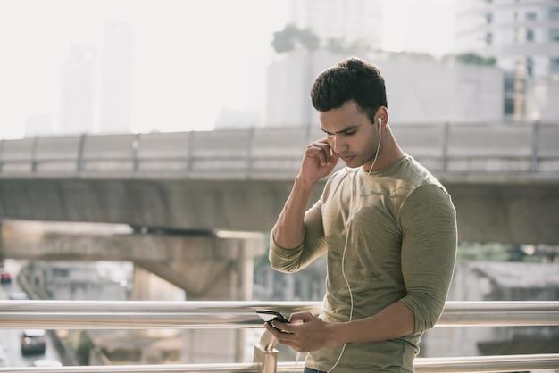 音楽を聴くイヤホンを着ている若いハンサムなインド人