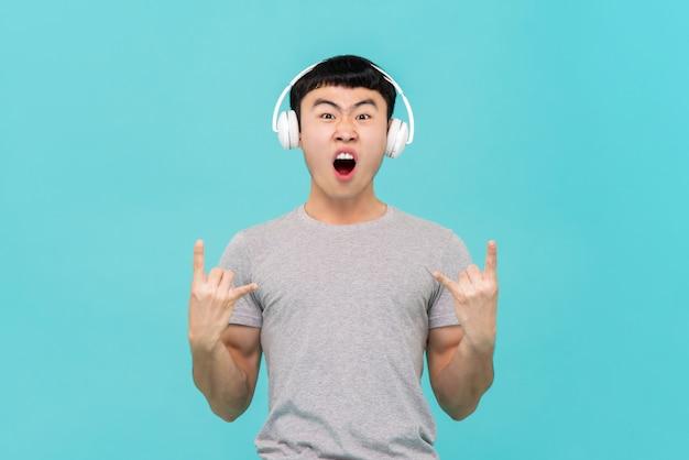 アジア人の男性が音楽を聴くヘッドフォンを着て