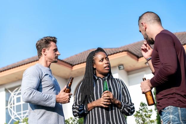 裏庭でアルコールを飲む多様な友達のグループ