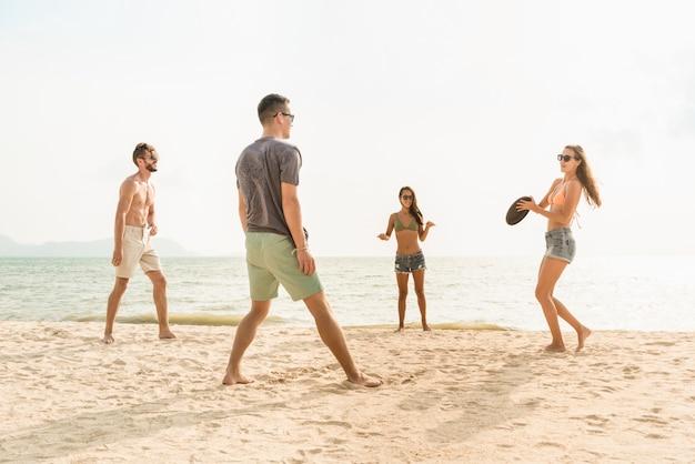 Группа друзей играет скользящий диск на пляже