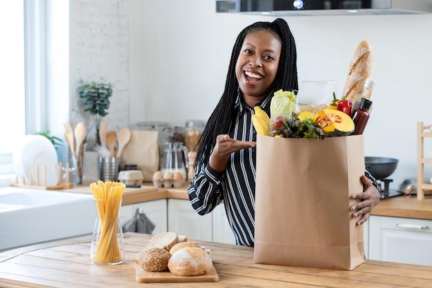 Женщина с продуктовой сумкой на кухне