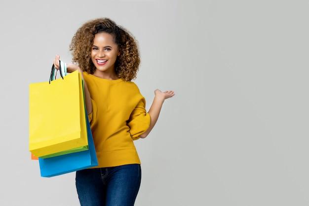 若いアフリカ系アメリカ人女性は買い物袋を持っています。