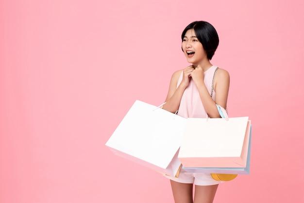驚きと興奮のジェスチャーで買い物袋を運ぶ若いアジア女性
