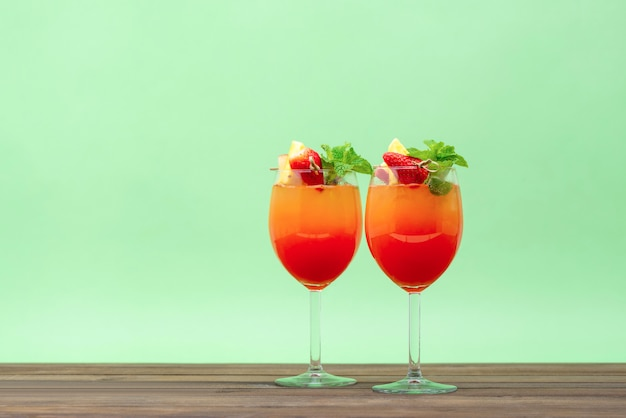 グラスで日の出フルーツカクテルを飲む