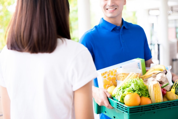 配達人の女性に食料品を配達