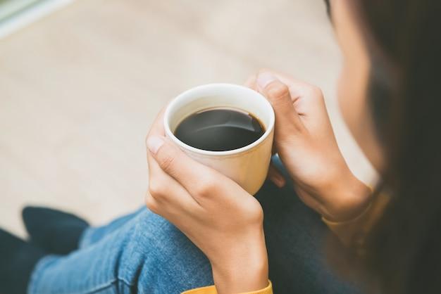 自宅でリラックスできるホットブラックコーヒーのカップを保持している女性