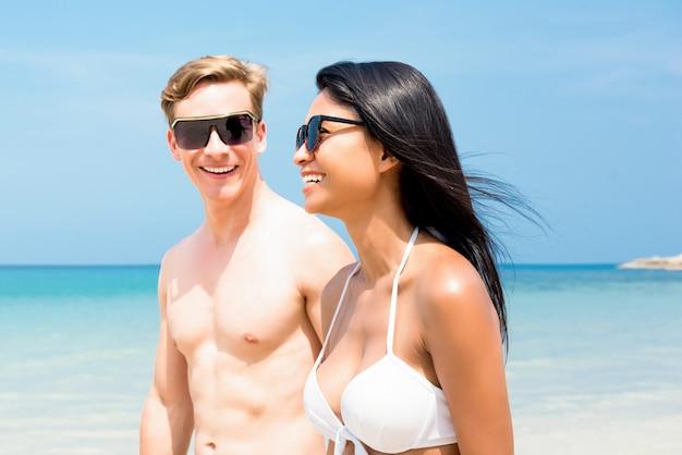 若い異人種間の観光客カップル、ビーチに沿って散歩