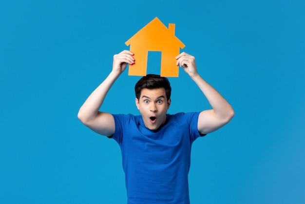 住宅モデルの頭上を保持している興奮した男