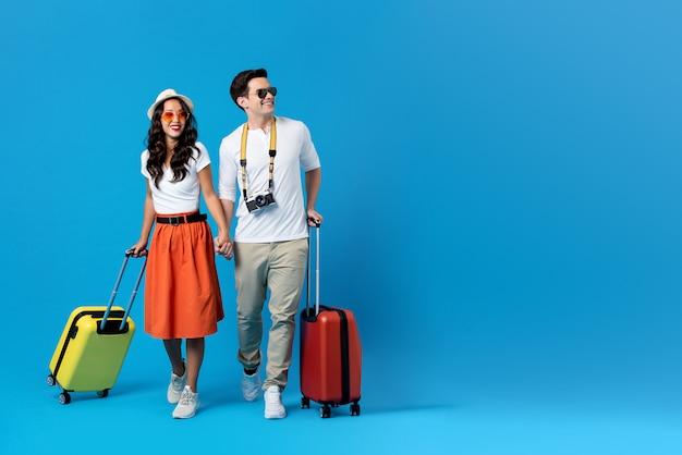 Молодая пара собирается на каникулы с разноцветными чемоданами