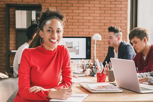 オフィス会議でカジュアルな赤いトップの黒のビジネス女性
