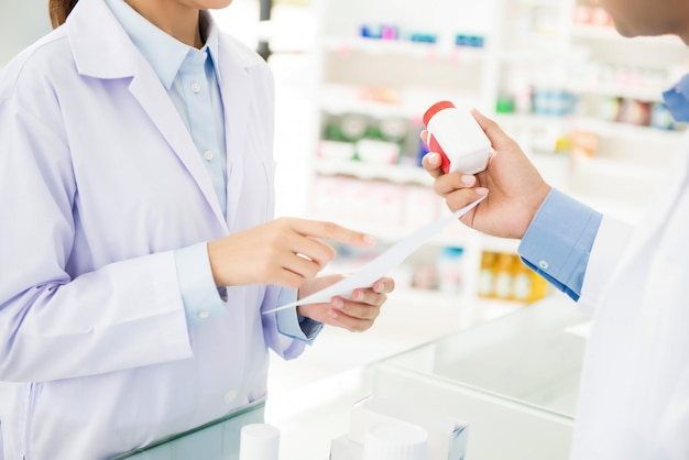 Аптекари показывая бутылку медицины и обсуждая отпускаемое по рецепту лекарство в аптеке.