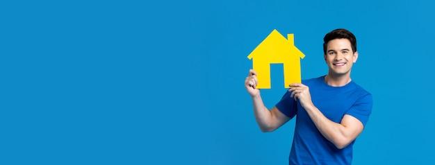 Улыбающийся красивый кавказский человек, держащий модель дома
