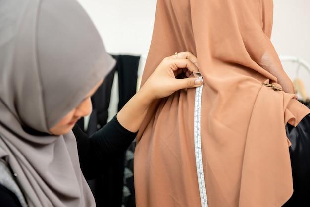 女性のイスラム教徒のデザイナーが服のサイズを測定