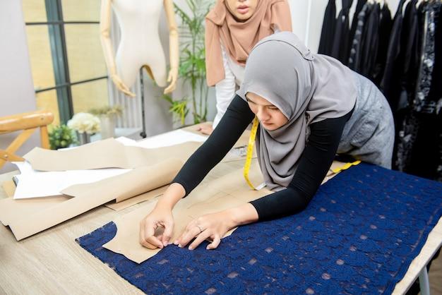 Мусульманская женщина модельер, закрепляющий бумажный узор на ткани