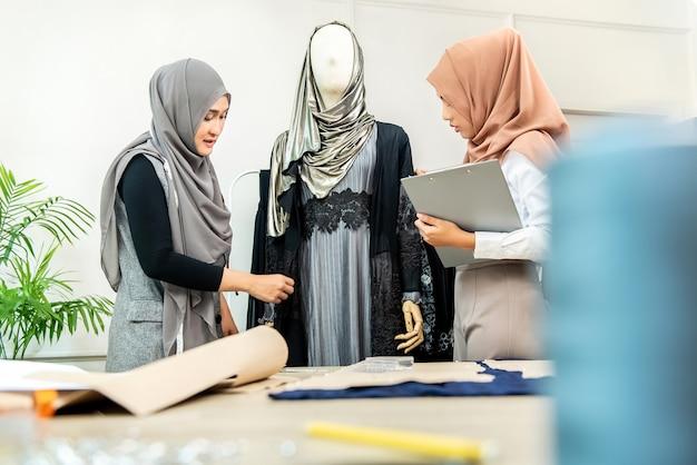 新しいコレクションに取り組んでいるイスラム教徒のドレスメーカー