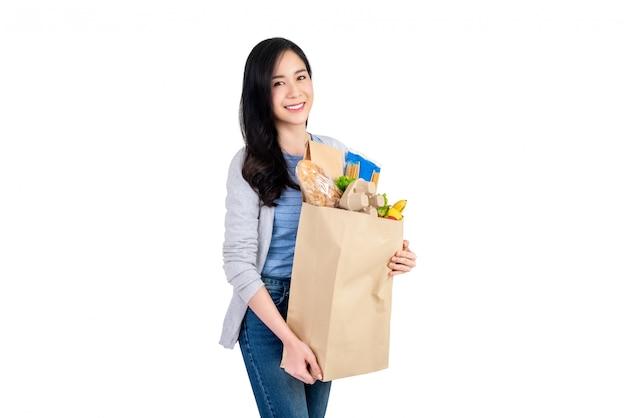 食料品の買い物袋を保持している美しいアジアの女性