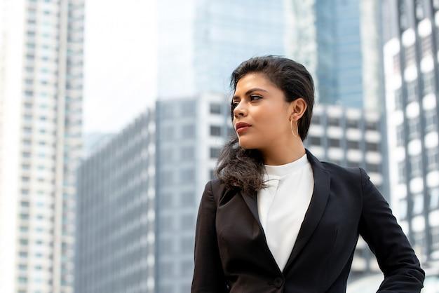 屋外に立っているフォーマルな服装の女性実業家