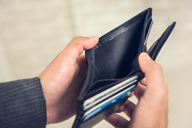 お金がないと空の財布を示す男の手