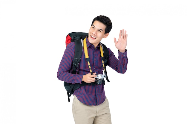 Портрет молодого счастливого азиатского путешественника, улыбаясь и махнув рукой