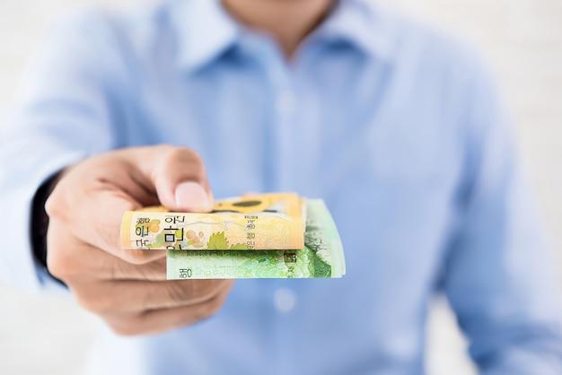 お金を与えるカジュアルなビジネスマン、韓国ウォンの紙幣