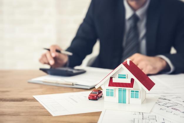 不動産プロジェクト契約に署名する前に予算を計算する実業家