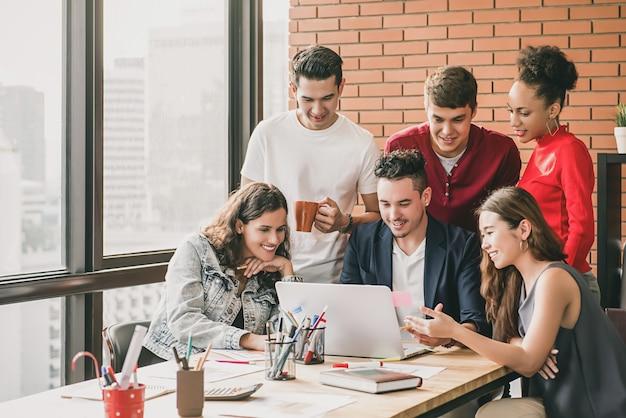 同僚のプロジェクトを観察する若いデザイナーのチームがオフィスで働いています。