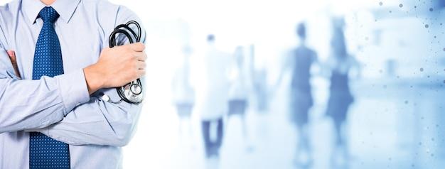Доктор держа стетоскоп стоя с рукой пересек в прихожую больницы