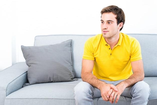 リビングルームのソファに座っている若いハンサムな男