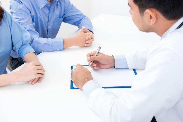 Доктор, консультирующийся с молодой парой пациентов