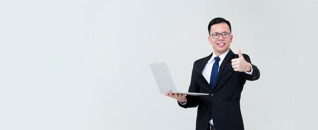 Молодой азиатский бизнесмен будучи счастлив с его компьтер-книжкой нося его дела и давая большие пальцы руки вверх