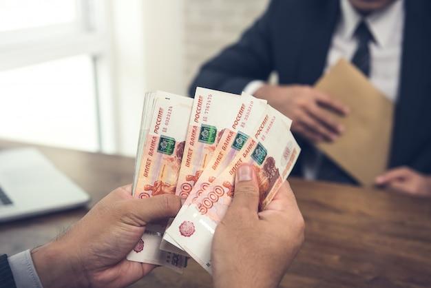 合意を行った後に与えられたロシアルーブルお金紙幣を数える実業家
