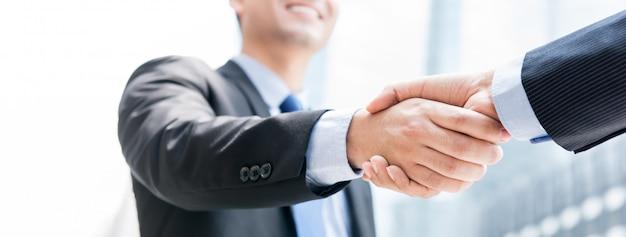 Улыбающийся бизнесмен делает рукопожатие со своим партнером на открытом воздухе в городе