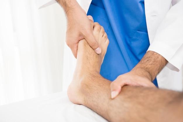 男性の医師または理学療法士が足の骨折患者に治療を与える