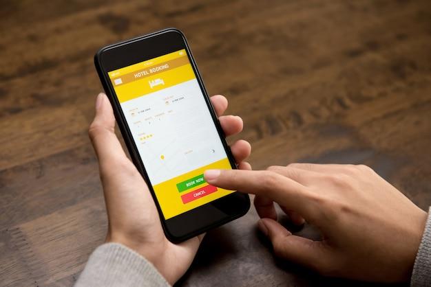スマートフォンのアプリケーションを使用してオンラインでホテルを予約する女性