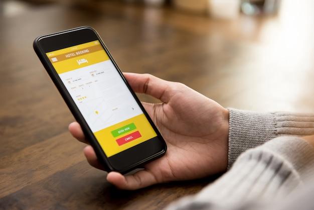 スマートフォンのアプリケーションでオンラインでホテルを予約する女性