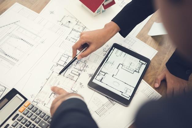フロアプランの青写真を議論する建築家やインテリアデザイナー