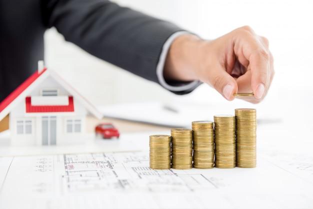 ぼやけた家モデルとお金のスタックの上にコインを置くビジネスマン