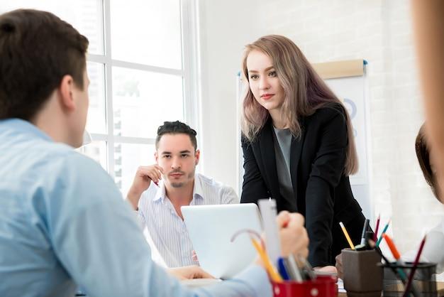 Женщина-лидер стоит и обращает внимание на своего коллегу на встрече