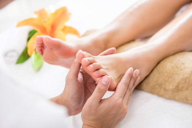 Терапевт дает расслабляющий традиционный рефлексологический массаж ступней женщине в спа