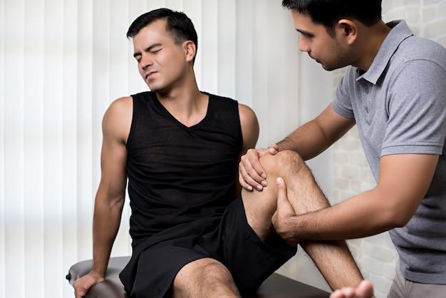 アスリートの男性患者を治療する理学療法士