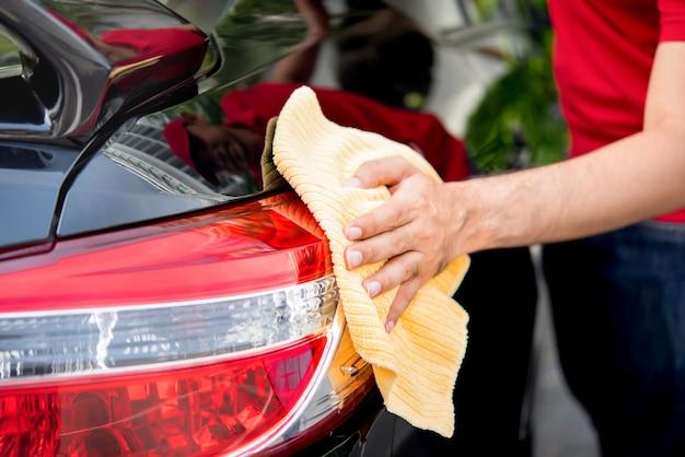 男性の自動ケアサービススタッフがマイクロファイバーの布で車のテールライトをクリーニング