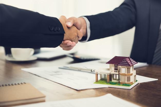 Агент по недвижимости или архитектор делают рукопожатие с клиентом на встрече