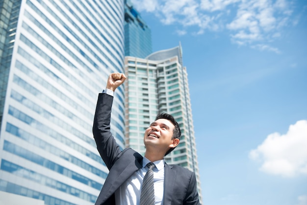 空中で彼の拳を上げる幸せ喜んで強力なアジア系のビジネスマン