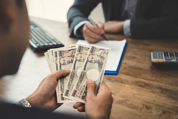 パートナーと契約を締結しながら、お金、日本円通貨を数える実業家