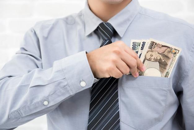 実業家は日本の紙幣のお金をシャツのポケットに入れる
