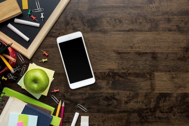 文房具、教育用品、木製テーブル背景にスマートフォンを含む学習機器